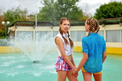Best girlfriends teenagers holding hands. Best girlfriends teenagers holding hands at the fountain in summer park. Girls dressed in shorts and a shirt. On Stock Photo
