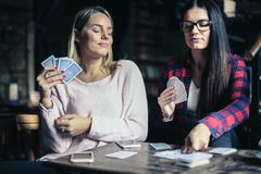 Best girls friends playing game card at home. stock image