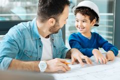Cute boy helping his father to draw a blueprint. Best help. Adorable little boy sitting at the table next to his father and helping him to draw a blueprint while Royalty Free Stock Photography