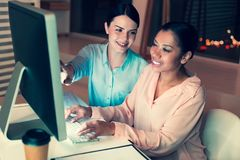 Cheerful woman suggesting ideas for project to her colleague. Best help. Charming young women sitting next to her female colleague and suggesting her some ideas stock photography