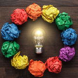 Best idea concept with crumpled colorful paper. Circle and light bulb in the centre on wooden table Royalty Free Stock Photography