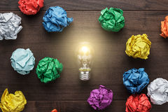 Best idea concept. With crumpled colorful paper and light bulb on wooden table Stock Images
