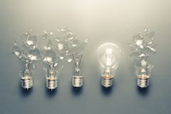 Best Idea Solution. Perfect light bulb glowing in a row of broken bulb for solution concept Royalty Free Stock Image