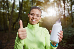 The best isotonic drink for sportsmen. Beautiful sportswoman holding bottle of isotonic drink and showing thumb up Stock Photography