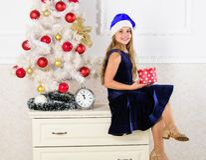 Best for kids. Kid girl near christmas tree hold gift box. Child celebrate christmas at home. Little girl santa hat stock image