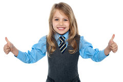 Best of luck for examinations. Smiling girl kid showing double thumbs to camera Royalty Free Stock Image