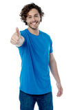 Best of luck mate !. Casual young man showing thumb up gesture Royalty Free Stock Photography