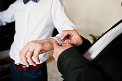 Best man helped stylish groom wear cuff links at wedding day. Stock Photography