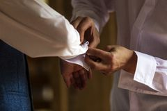 Best man helping groom with cufflinks Royalty Free Stock Image