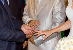 Best man puts the ring on a brides finger Stock Images