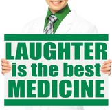 The Best Medicine. A doctor holding a conceptual sign Stock Photos