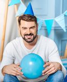 Pleasant man in party hat posing with balloon Stock Photos