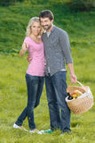 That is the best place for picnic. Loving young couple is going Royalty Free Stock Image
