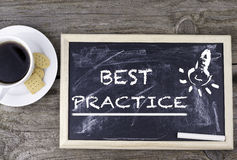 Best practice. Chalk board on a wooden table Royalty Free Stock Image