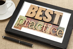 Best practice on digital tablet. Best practice -  words in vintage letterpress wood type on digital tablet screen with a cup of coffee Stock Image