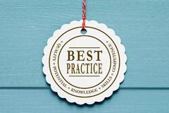 Best practice label. A white label with the text 'Best Practice' on blue wood background stock photos