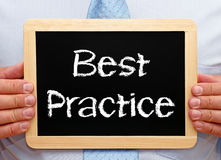 Best Practice - Manager holding chalkboard with text. In his hands royalty free stock images