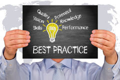 Best Practice - Manager holding sign with light bulb and text. On world map background Royalty Free Stock Images