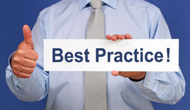 Best practice sign. Body of businessman with thumb up holding best practice sign Royalty Free Stock Photography
