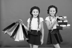 Best price. Buy now. Visit shopping mall. Kids girls hold bunch shopping bags or birthday gifts packages. Dreams come. True. Happy childhood. Shopping concept stock photo