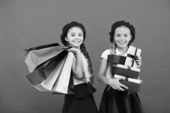 Best price. Visit shopping mall. Kids girls hold bunch shopping bags or birthday gifts packages. Dreams come true. Happy. Childhood. Shopping concept. Child royalty free stock image