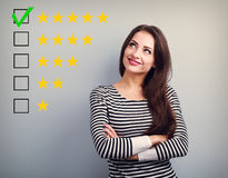 The best rating, evaluation. Business confident happy woman voti. Ng to five yellow star to increase ranking. On grey background royalty free stock images