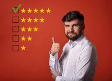The best rating, evaluation, online rewiew. Happy bearded business showing the hand thumb up in white shirt on red background wi. Th empty space background stock photography