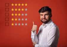 The best rating, evaluation, online rewiew. Happy bearded business showing the hand thumb up in white shirt on red background wi. Th empty space royalty free stock photo