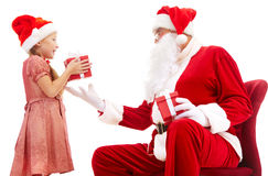 Best regards. Image of cute girl taking Christmas present from Santa Royalty Free Stock Images