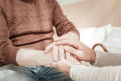 Close natives holding hands each other. Best relationship. Close reliable natives being together in the spacious room holding hands each other Royalty Free Stock Photo
