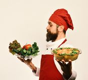 Best salads from chef. Handsome waiter or cook in uniform. Best salads from our chef. Handsome waiter or cook in uniform stretching out exquisite salad on the stock images