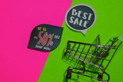 Best Sale and Up To -50% Off Shop Now Text and Shopping cart. Discount and promotion business concept on colorful background. N royalty free stock image