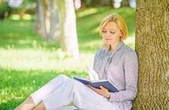 Best self help books for women. Books every girl should read. Girl concentrated sit park lean tree trunk read book. Reading inspiring books. Bestseller top royalty free stock photos