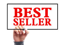 Best Seller. Hand with marker is writing the concept of Best Seller on the transparent whiteboard royalty free stock image