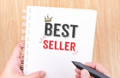 Best seller word on white ring binder notebook with hand holding royalty free stock images