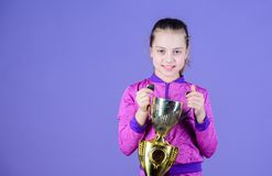 She is the best. Small girl holding silver cup. Little child with cup shaped sports trophy. Cute athlete being awarded. With cup. Adorable cup winner, copy stock image