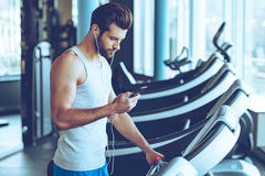 Best song for his training. Side view of young handsome man in sportswear using his smart phone while standing on treadmill at gym stock image