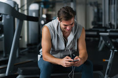 Best song for his training. Young handsome man in headphones using his smart phone and listening to music. Young man taking a break after his workout and royalty free stock photography