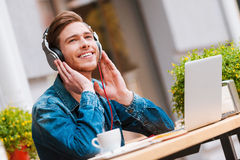 The best start of my day!. Cheerful young man holding hands on headphones while sitting at sidewalk cafe royalty free stock photo