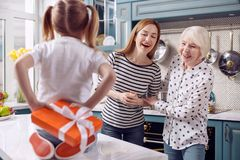 Happy women waiting for present from little girl. Best surprise. Charming young women and her senior mother trying to guess what kind of present their little Stock Image