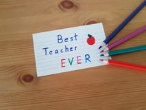 Best Teacher Ever. Sign with colored pencils laying on a wooden background, School supplies, Back to school, Kindergarten and Elementary students royalty free stock image