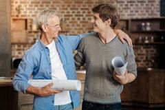 Cheerful colleagues hugging each other and holding blueprints royalty free stock photography