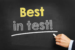 Best in test!. Hand with chalk writing Best in test! on a blackboard Royalty Free Stock Photos