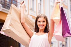 The best therapy is shopping. Attractive young woman holding shopping bags and smiling while standing outdoors Royalty Free Stock Photography