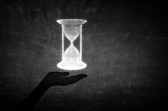 Best time is now. Close up of businessman hand holding sandglass icon in palm Stock Image