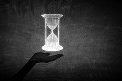 Best time is now. Close up of businessman hand holding sandglass icon in palm Royalty Free Stock Photo