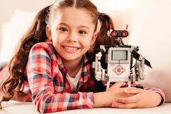 Beaming little girl embracing her new robot toy. The best toy ever. Cute brunette kid grinning broadly into the camera while lying on a sofa and hugging her new Royalty Free Stock Image