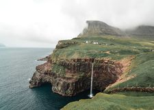 The best view of Mulafossur, a stunning waterfall in the Faroe Island of Vagar. In the town of Gasadalur royalty free stock images