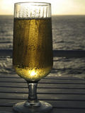 Best Way to End the Day. Glass of Beer illuminated by the sunset with the ocean in the background Royalty Free Stock Images