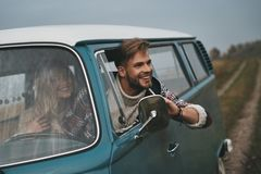 Best way to escape from the city. Handsome young men leaning out the van?s window and smiling while sitting on the front passenger seats together with Stock Photo